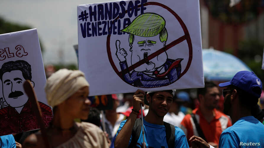 A supporter of Venezuela's President Nicolas Maduro holds a placard depicting U.S. President Donald Trump during a rally in Caracas, Sept. 19, 2017.