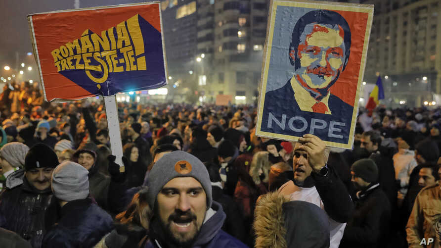 "People hold posters depicting the leader of the ruling Social Democratic party, Liviu Dragnea, the other reading ""Romania-Wake Up"" during a protest in Bucharest, Romania, Feb. 1, 2017."