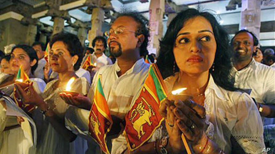 Sri Lankan performing artists hold national flags and lamps as they stage a peaceful protest against a UN report that gives credence to allegations the government and Tamil Tiger rebels may have committed war crimes as the country's civil war drew to