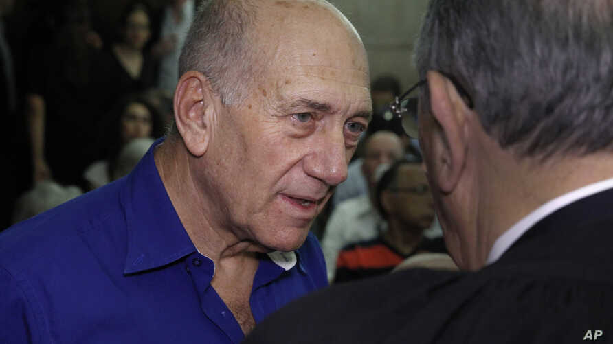 Israel's former Prime Minister Ehud Olmert speaks to a lawyer upon his arrival at the Tel Aviv District Court in Israel, Tuesday, May 13, 2014. Olmert was sentenced on Tuesday to six years in prison for his role in wide-ranging bribery case, capping