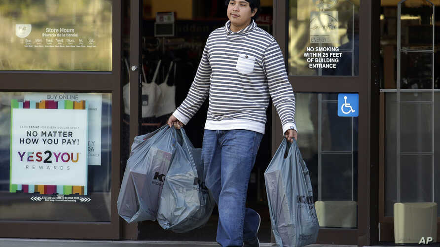 A man carries bags out of a department store, in Alameda, California, Dec. 17, 2015. U.S. consumer spending rebounded in Nov. after a weak showing in Oct., while a key inflation gauge posted the fastest year-over-year increase in 11 months.