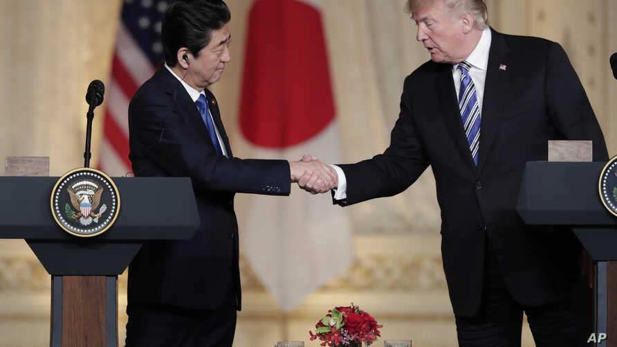 Japanese Prime Minister Shinzo Abe, left, and President Donald Trump shake hands during a news conference at Trump's private Mar-a-Lago club, April 18, 2018, in Palm Beach, Florida.