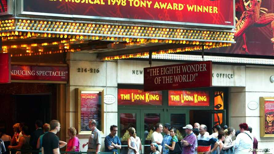 """FILE - People wait for tickets outside of the Broadway musical """"The LionKing,"""" in New York City."""