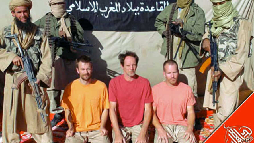 European hostages being held by Al Qaeda are surrounded by masked men holding guns in an undisclosed location in Mali (December 2011 file photo)