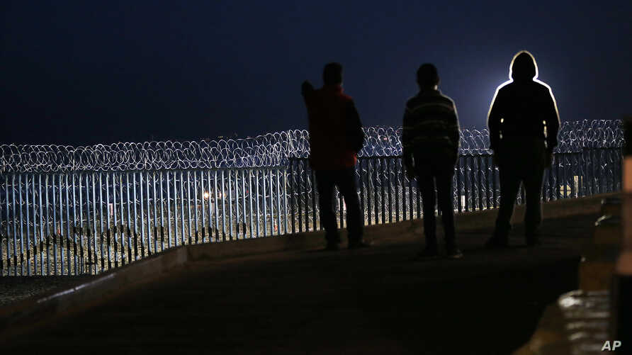 Residents stand on a hill before barriers, wrapped in concertina wire, separating Mexico and the United States, where the border meets the Pacific Ocean, in Tijuana, Mexico, Nov. 17, 2018. Many of nearly 3,000 U.S.-bound Central American migrants hav