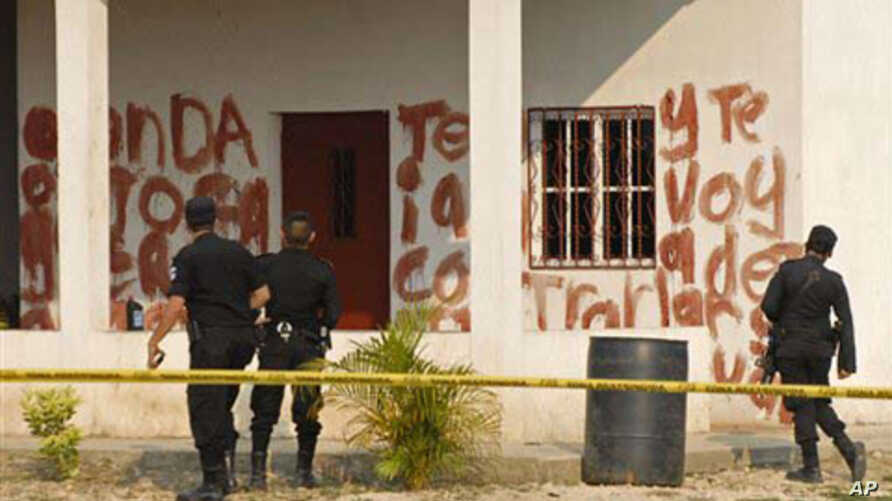 Police agents look at a message written in blood at the site of a massacre at a local ranch in the hamlet Caserio La Bomba, in La Libertad, northern Guatemala, Sunday May 15, 2011