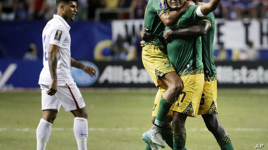 Jamaica's Rudolph Austin, facing camera, celebrates with teammates Joel McAnuff, left, and Je-Vaughn Watson, right, as United States' DeAndre Yedlin walks off the pitch after Jamaica defeated the United States 2-1 in a CONCACAF Gold Cup soccer semifi
