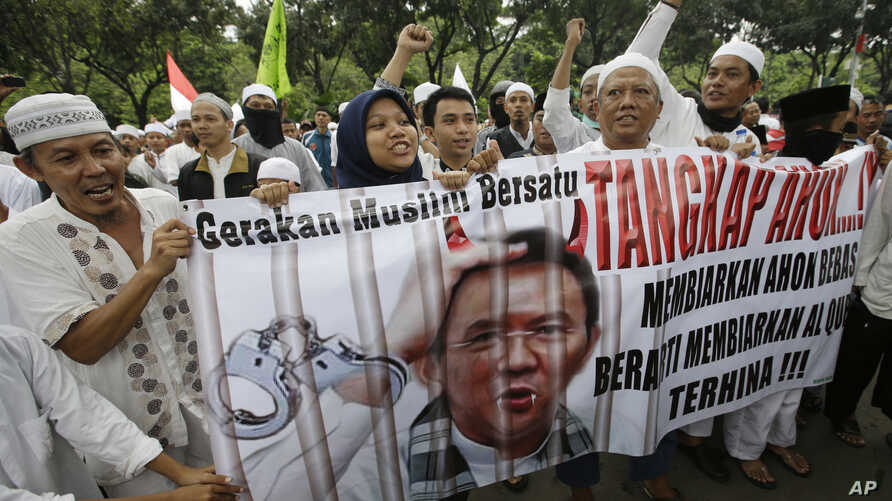 "Indonesia Protest: In this Friday, Oct. 14, 2016, photo, Muslim protesters hold a banner calling for the arrest of Jakarta's ethnic Chinese and Christian Governor Basuki Tjahaja Purnama, popularly known as ""Ahok"", outside the City Hall. Indonesian po"