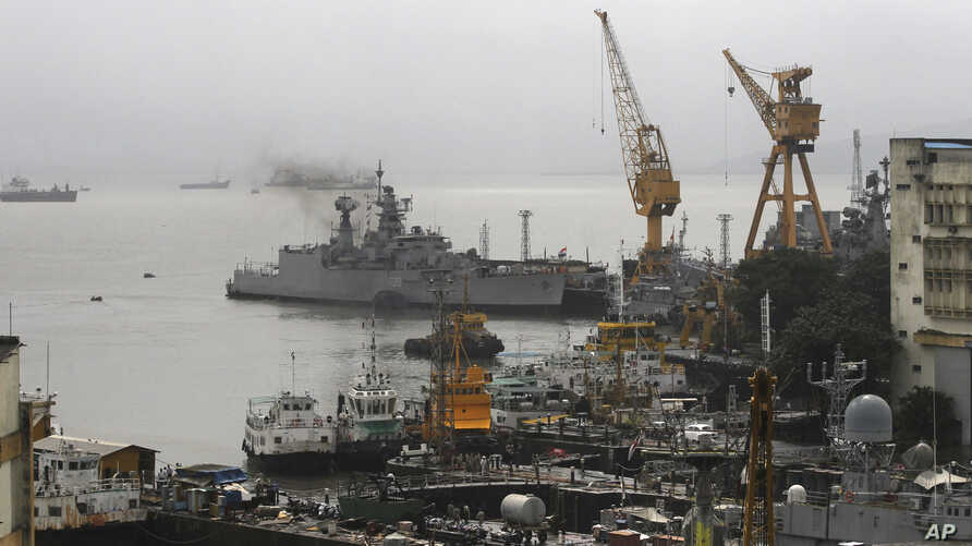 Ships ride at anchors at a naval dockyard where a submarine caught fire and sank after an explosion early Wednesday in Mumbai, August 14, 2013.