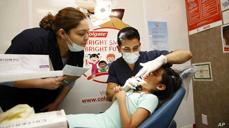 FILE - UT Health Dental School student volunteers provide a free dental screening on a child as part of Colgate's Oral Health Month at Fiesta Mart in Houston, June 13, 2015.