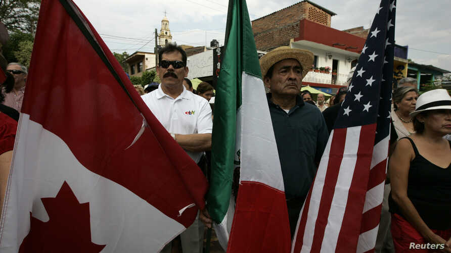 A resident holds the flags of Canada, Mexico and the U.S. during a meeting with local police officials in the town of Ajijic, in the Mexican State of Jalisco, May 16, 2012. About 400 U.S. and Canadian citizens gathered on Wednesday to meet with offic
