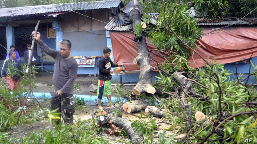 Workers clear the road off toppled trees after Typhoon Yutu slammed Isabela province in northeastern Philippines, Oct. 30, 2018.