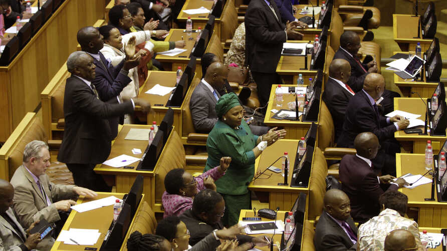Members of the ruling African National Congress applaud as the results are read of a no-confidence vote by MP's in parliament in Cape Town South Africa, Aug. 8, 2017.
