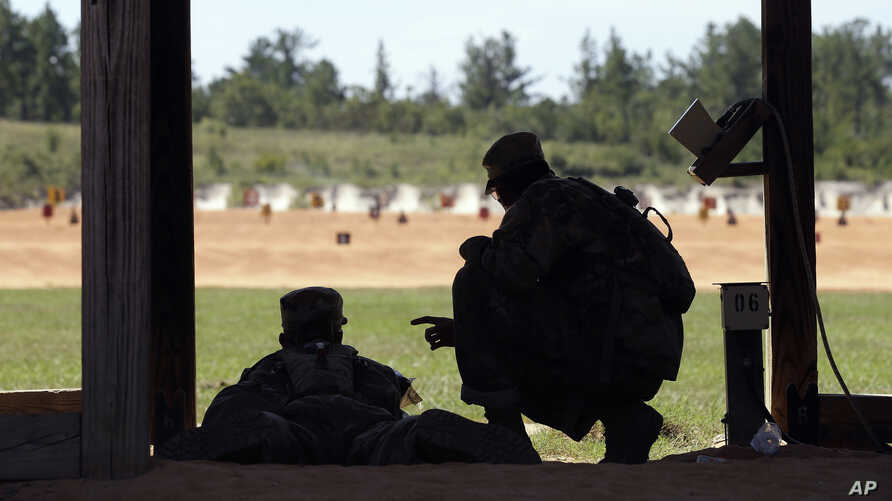 FILE - A U.S. Army recruit is instructed by a drill sergeant, right, during live-fire marksmanship training at Fort Jackson, S.C., Aug. 17, 2016.
