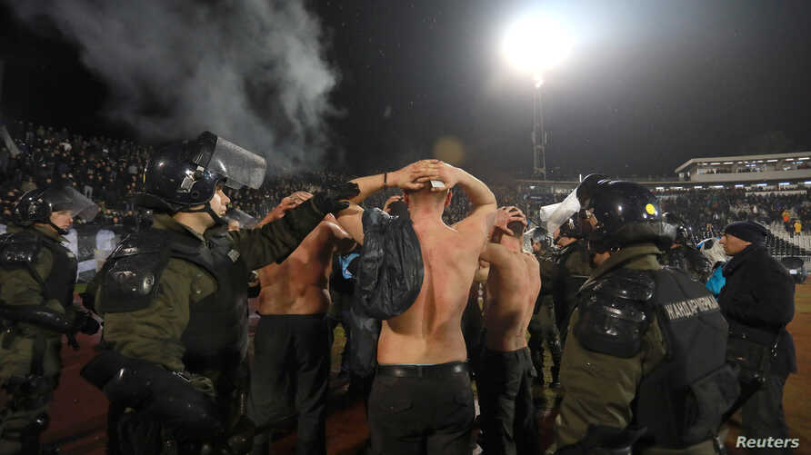 Police escort the soccer fans injured during the fights at a match between Red Star and Partizan in Belgrade, Dec. 13, 2017.