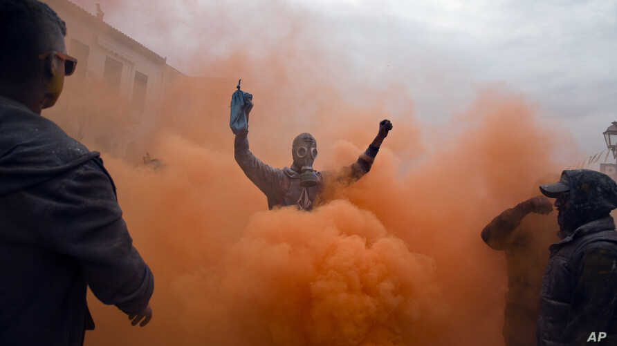Revelers throw flour as they participate in the flour war, a unique colorful flour fight marking the end of the carnival season, in the port town of Galaxidi, Greece, Feb. 19, 2018.