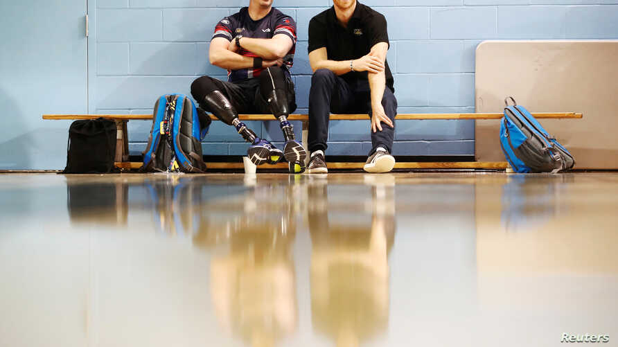 Britain's Prince Harry sits with an athlete at the Toronto Pan Am Sports Centre ahead of the Invictus Games in Toronto, Sept. 22, 2017.