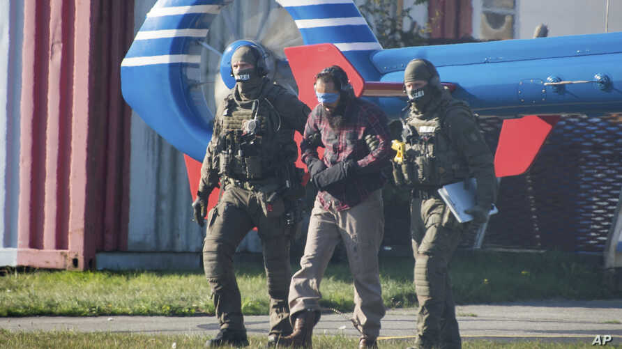 Terrorist Mounir el Motassadeq is led from one helipcopter to another at the airport in Hamburg, northern Germany, Oct. 15, 2018.