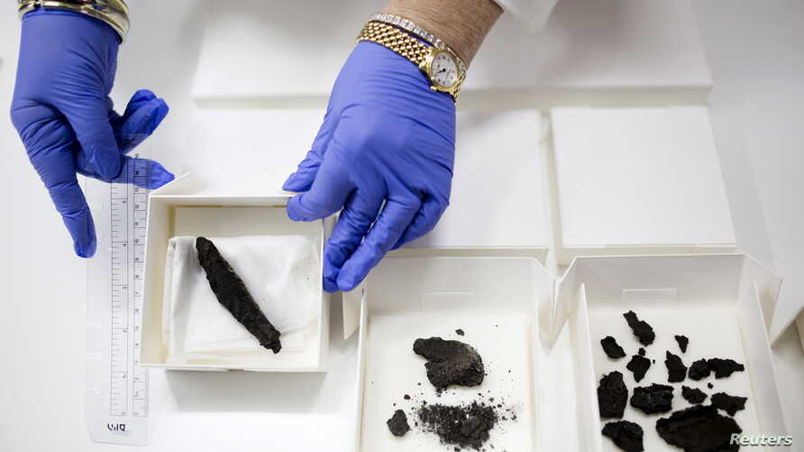 An Israel Antiquities Authority worker displays a scroll (L), found in 1970, along with other findings, that are yet to be analyzed, at the Israel Museum in Jerusalem, July 20, 2015.
