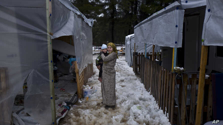 Shireen Daoud, 25 and three months pregnant, a Syrian refugee from al-Hasaka, holds her son Herman, 2, while posing for a picture by the entrance of her shelter, during snowfall at the refugee camp of Ritsona, Greece, Dec. 29, 2016. Squalid condition