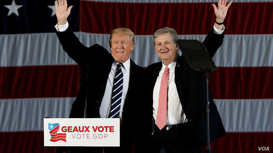 "U.S. President-elect Donald Trump waves with John Kennedy, who won the race Saturday for a seat in the U.S. Senate  from Louisiana, during a ""Thank You USA"" tour rally in Baton Rouge, Louisiana, Dec. 9, 2016."