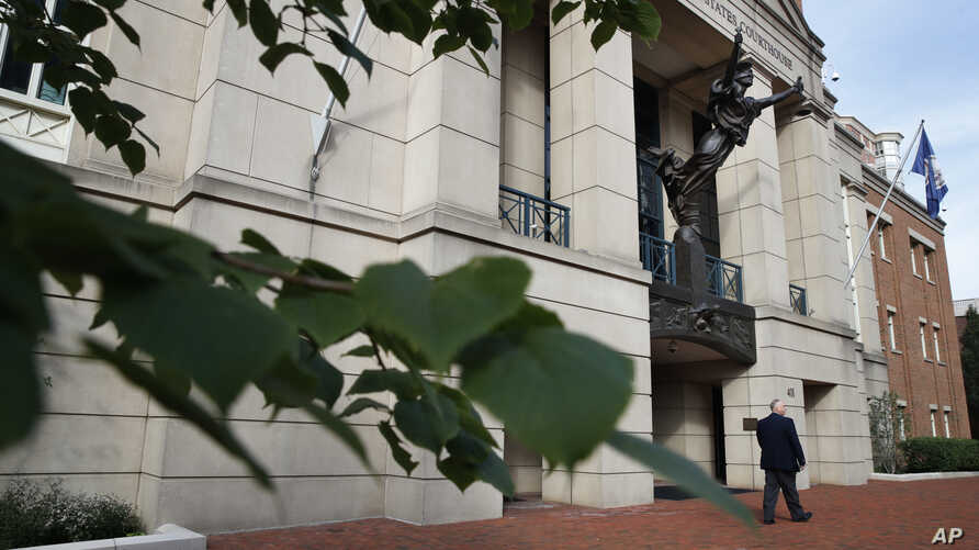 A security guard walks by the front of federal court as jury deliberations begin in the trial of the former Trump campaign chairman, in Alexandria, Virginia, Aug. 16, 2018.