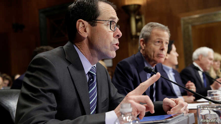 Chief Executive Officer of AT&T Randall Stephenson (L) speaks as Chairman and Chief Executive Officer of Time Warner Jeffrey Bewkes listens during testimony before the Senate Judiciary Committee Antitrust Subcommittee hearing on the proposed deal bet