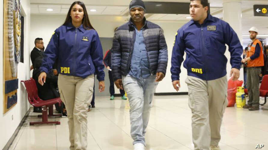 In this photo provided by the Policia de Investigacion de Chile, PDI, officers escort former heavyweight boxing champion Mike Tyson after he was denied entry to the country, at the international airport in Santiago, Chile, Nov. 9. 2017.