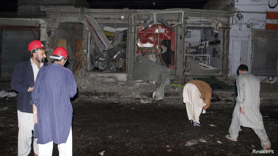 Rescue workers and security officials stand at the site of a suicide bomb attack on the outskirts of Rawalpindi near Islamabad, November 21, 2012.