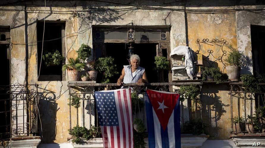 FILE - Javier Yanez stands on his balcony in Old Havana, where he hung U.S. and Cuban flags after learning that the two nations would begin restoring diplomatic ties, Dec. 19, 2014.