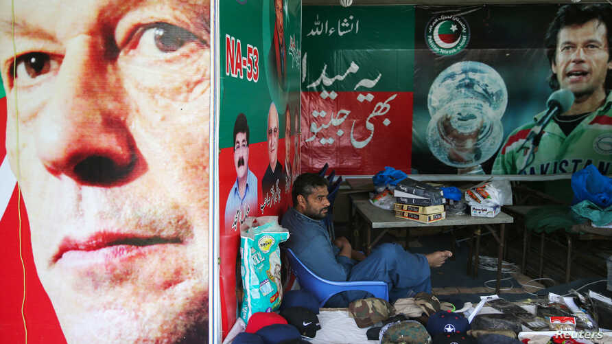 A vendor sits next to images of cricket star-turned-politician Imran Khan, chairman of Pakistan Tehreek-e-Insaf (PTI), at a market in Islamabad, Pakistan, July 27, 2018. Khan, who declared victory in this week's election, has called for better ties w