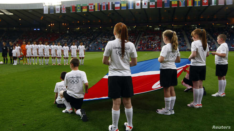Children hold the North Korean flag ahead of the women's Group G football match between North Korea and Colombia at the London 2012 Olympic Games in Hampden Park, Glasgow, Scotland July 25, 2012.