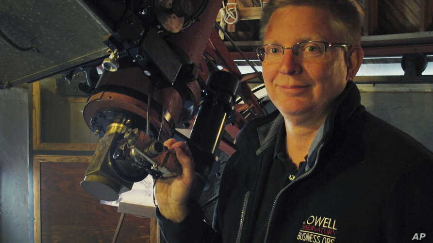FILE - Kevin Schindler of Lowell Observatory stands next to the Pluto telescope in Flagstaff, Arizona.
