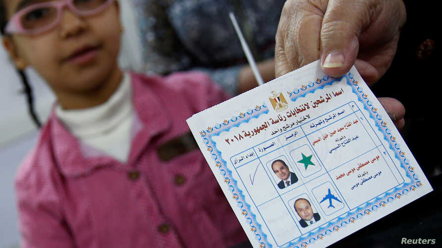 An Egyptian woman shows her ballot paper with a sign for Egypt's President Abdel Fattah el-Sissi before casting her vote during the first day of the presidential election at a polling station in Cairo, Egypt, March 26, 2018.