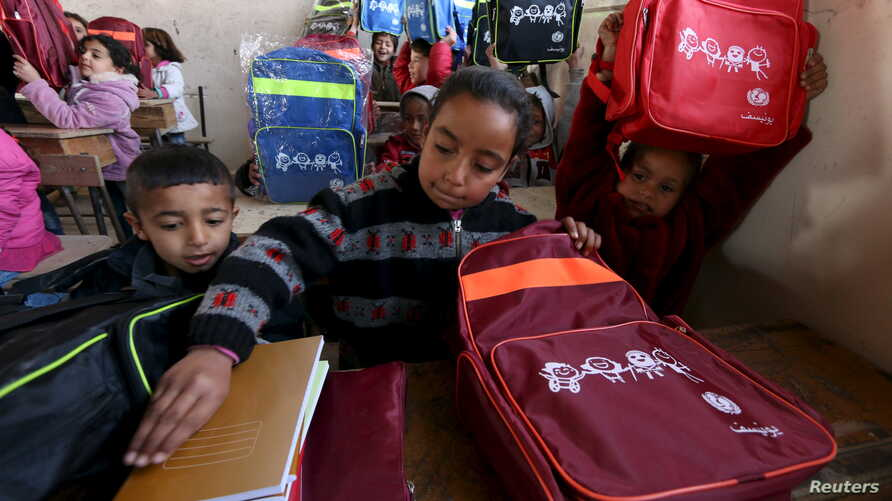 Syrian children unpack their backpacks — donated by UNICEF