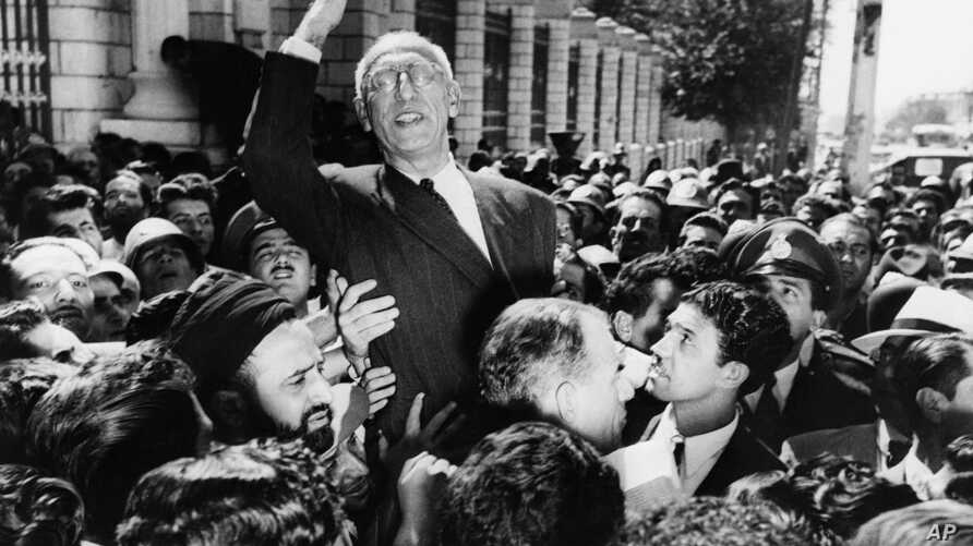 FILE - Prime Minister Mohammed Mosaddegh rides on the shoulders of cheering crowds in Tehran's Majlis Square, outside the parliament building, after reiterating his oil nationalization views to his supporters. Once expunged from its official history,