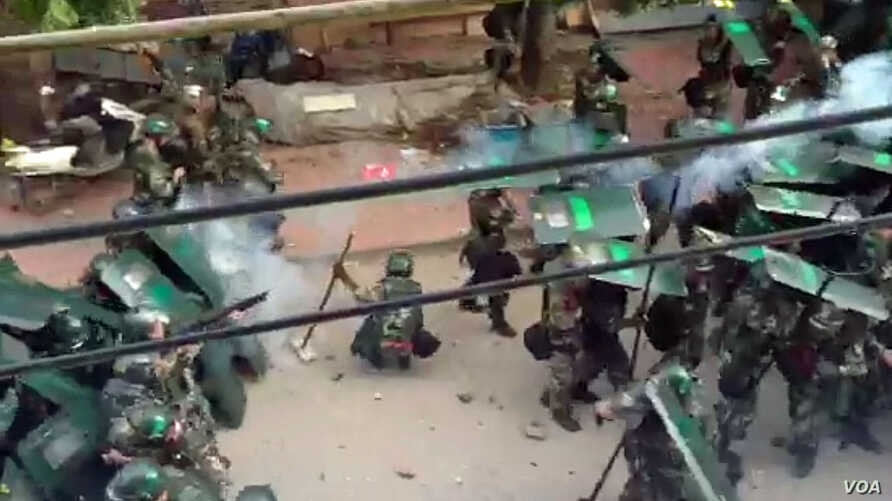 In a still image taken from not independently confirmed video, Chinese riot police are seen pushing against protesters in the coastal village of Wukan, in Guangdong province, China.