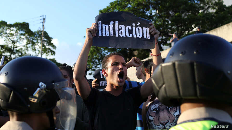 "FILE - An opposition supporter holding a placard that reads ""Inflation"" shouts slogans in front of riot police during a protest in Caracas, Venezuela, March 30, 2017."
