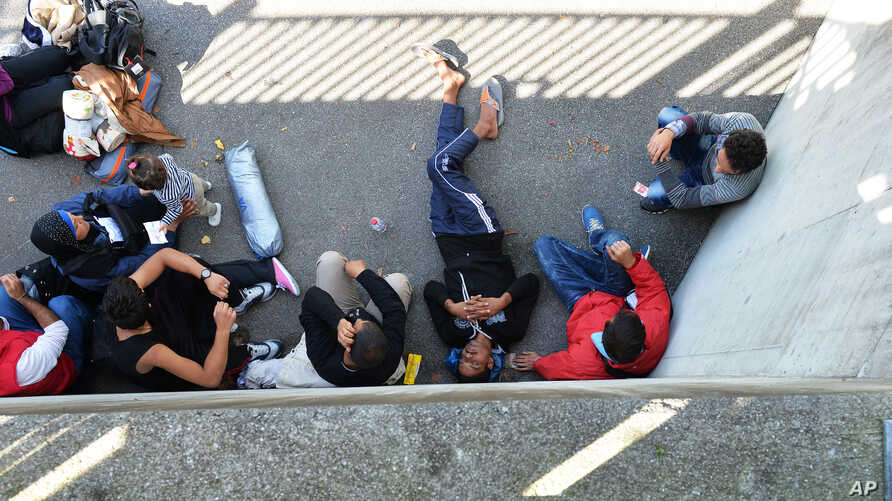 Refugees rest in the shadow after arriving in Freilassing at the border between Austria and Germany, southern Germany, Sept. 16, 2015.