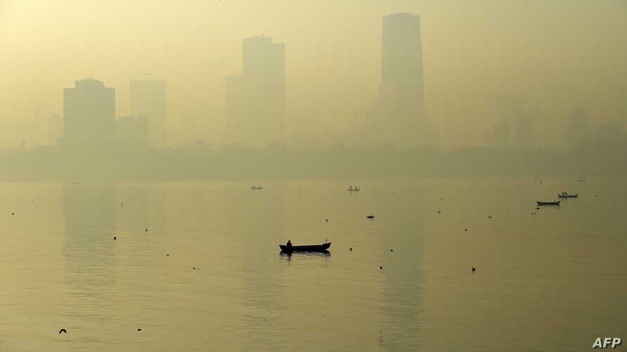 A fishing boat is seen in the morning general view of the city skyline covered by a smoggy haze in Mumbai, India, Jan. 29, 2016.