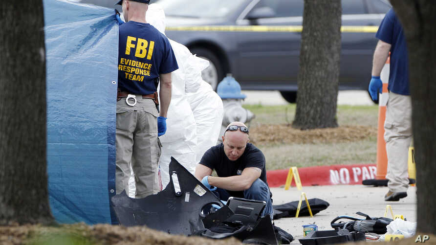 FBI crime scene investigators document the area around two deceased gunmen and their vehicle outside the Curtis Culwell Center in Garland, Texas, May 4, 2015.