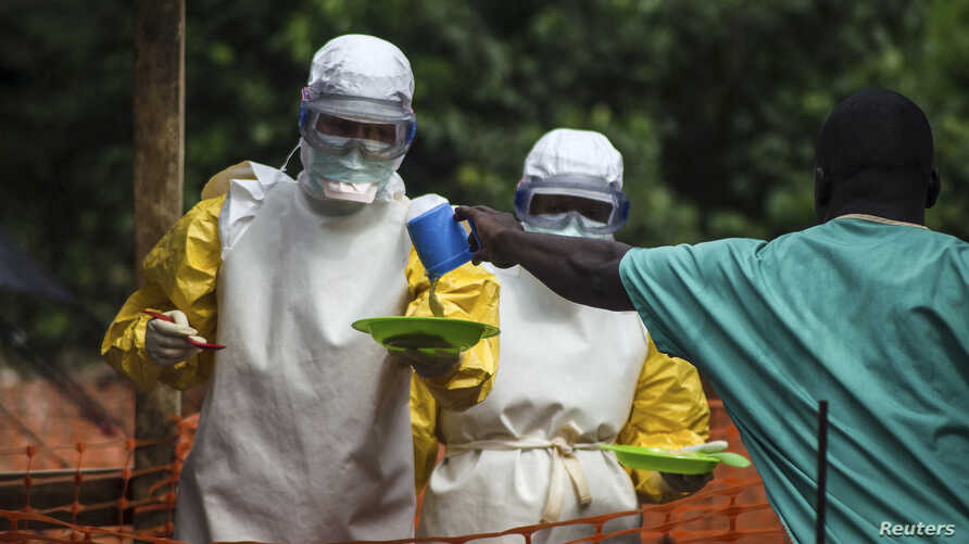 Medecins sans Frontieres (MSF) medical workers deliver food to patients kept in an isolation area at their Ebola treatment center in Kailahun on July 20.