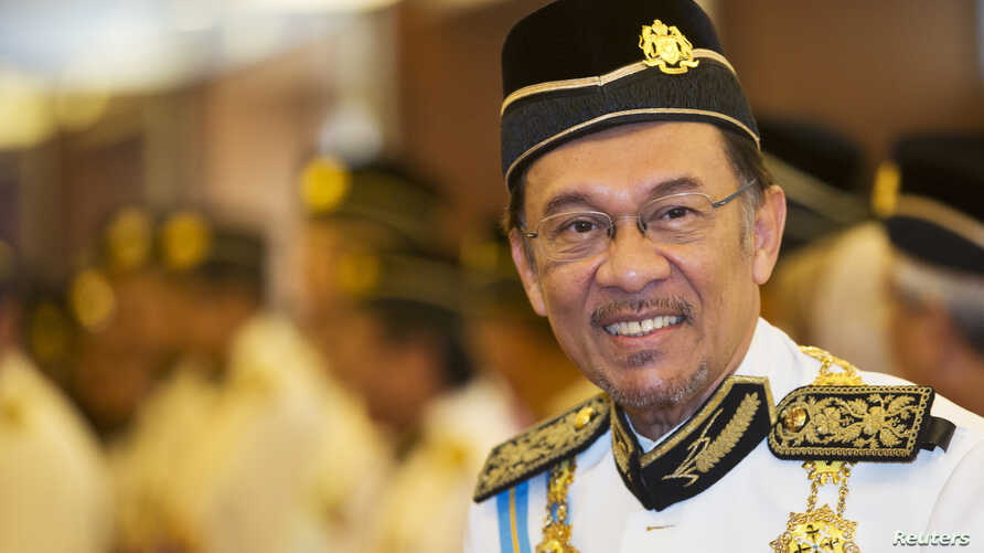 FILE - Malaysia's opposition leader Anwar Ibrahim smiles as he he arrives for the opening of the parliament sitting at Parliament House in Kuala Lumpur June 25, 2013.