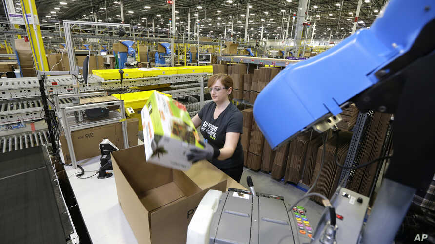 FILE - in this Feb. 13, 2015 file photo, a worker places an item in a box for shipment,at a Amazon.com fulfillment center in DuPont, Washington.