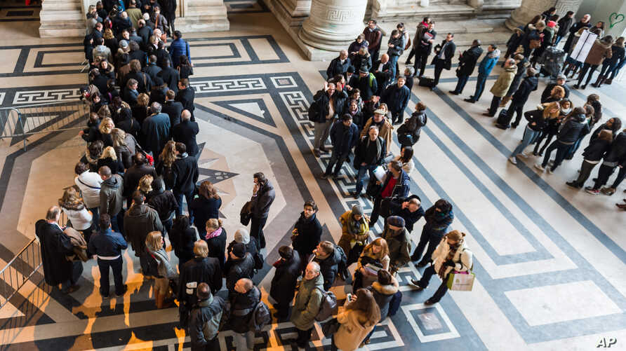 People queue as police controls everybody who wants to enter the Palace of Justice in Brussels, Friday, Jan. 16, 2015. Thirteen people were detained in Belgium and two arrested in France in an anti-terror sweep following a firefight in which two susp