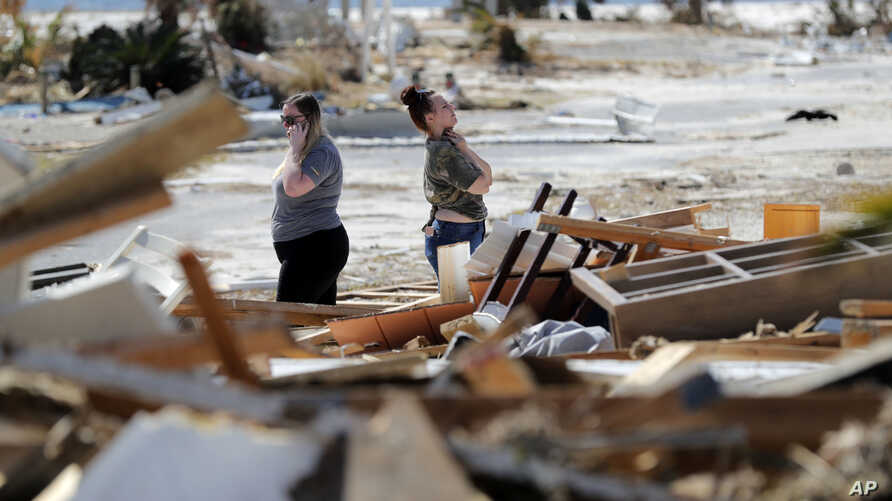 Christina Amanda, right, and Connie Huff, look for their possessions at the site of their destroyed home in the aftermath of Hurricane Michael in Mexico Beach, Fla., Oct. 17, 2018.