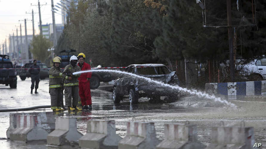Afghan firefighters clean up the site of a deadly suicide bombing, in Kabul, Afghanistan, Nov. 16, 2017.