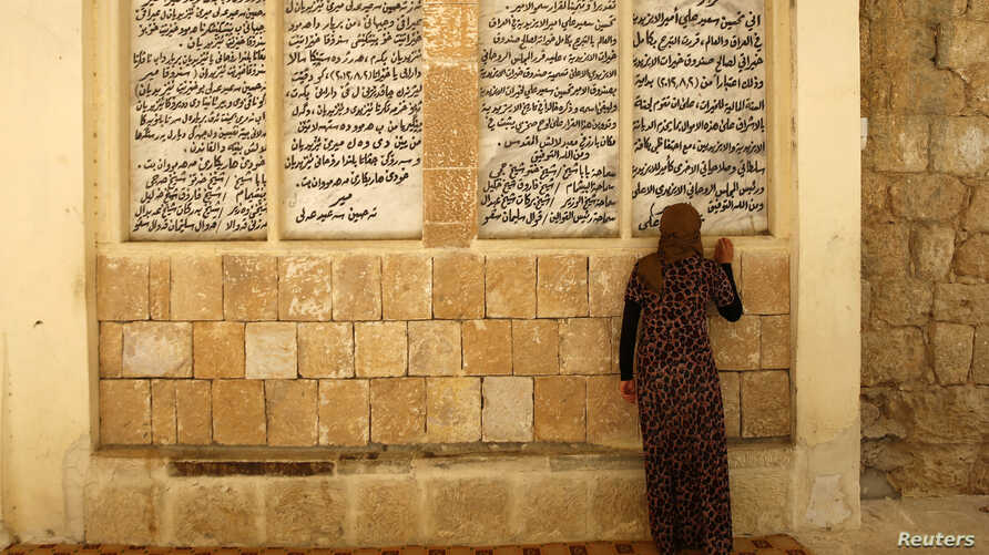 FILE - A displaced woman from the minority Yazidi sect, who fled violence in the Iraqi town of Sinjar, worships at their main holy temple in Lalish in Shikhan, Sept.  20, 2014. Followers of an ancient religion derived from Zoroastrianism, the Yazidi