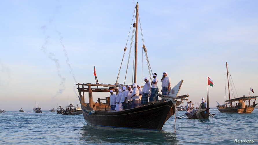 Men ride traditional wooden boats during the Katara Traditional Dhow Festival at Doha beach, Qatar Nov. 17, 2015.