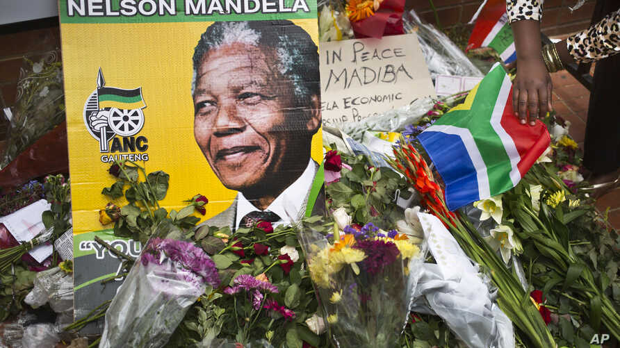 Flowers, posters, and messages left by mourners lie in front of Nelson Mandela's old house in Soweto, Johannesburg, South Africa, Saturday, Dec. 7, 2013.